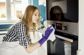 Beautiful blonde woman polishes stainless steel oven. On her hands protective rubber gloves.