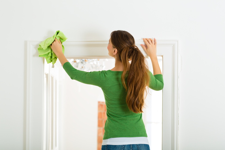 Cleaning dust from a door frame.
